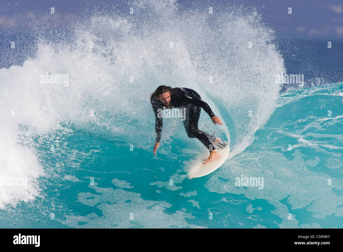 Surfer rides along azure blue wave. - Stock Image