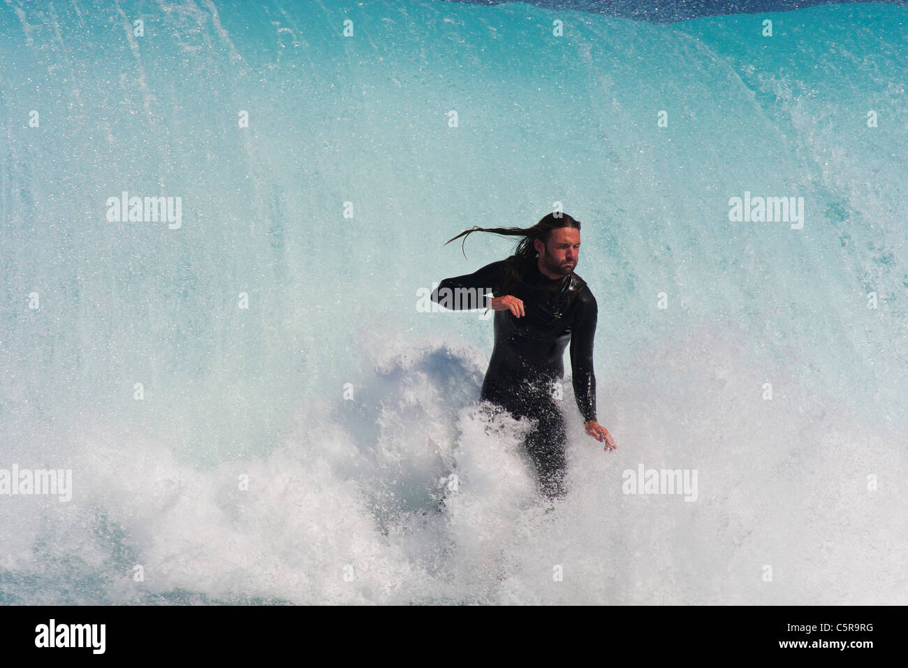 This surfer takes a deep breath as he is about to be taken out by the massive wave behind him. - Stock Image
