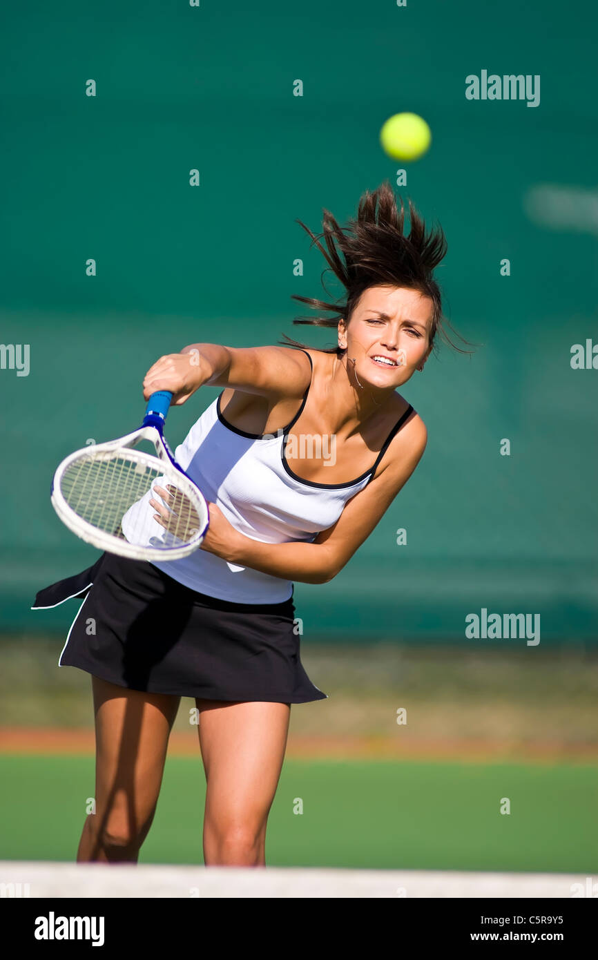 Tennis player smashes ball over net. - Stock Image