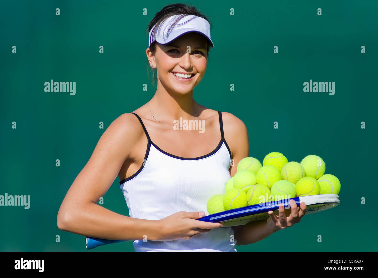 A tennis player with a welcoming smile on court. - Stock Image