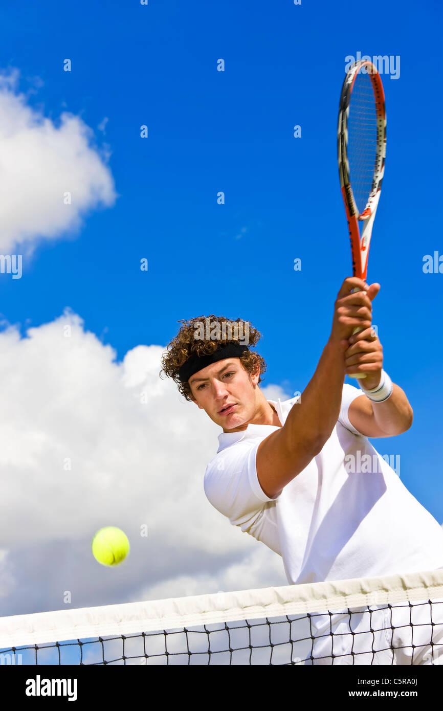 Tennis player returns the ball over net. - Stock Image