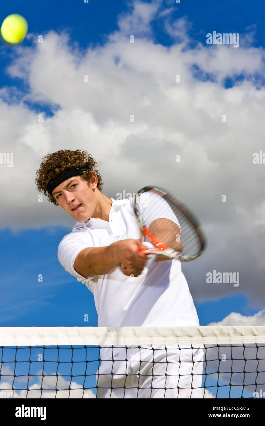 A tennis player returns at the net. - Stock Image