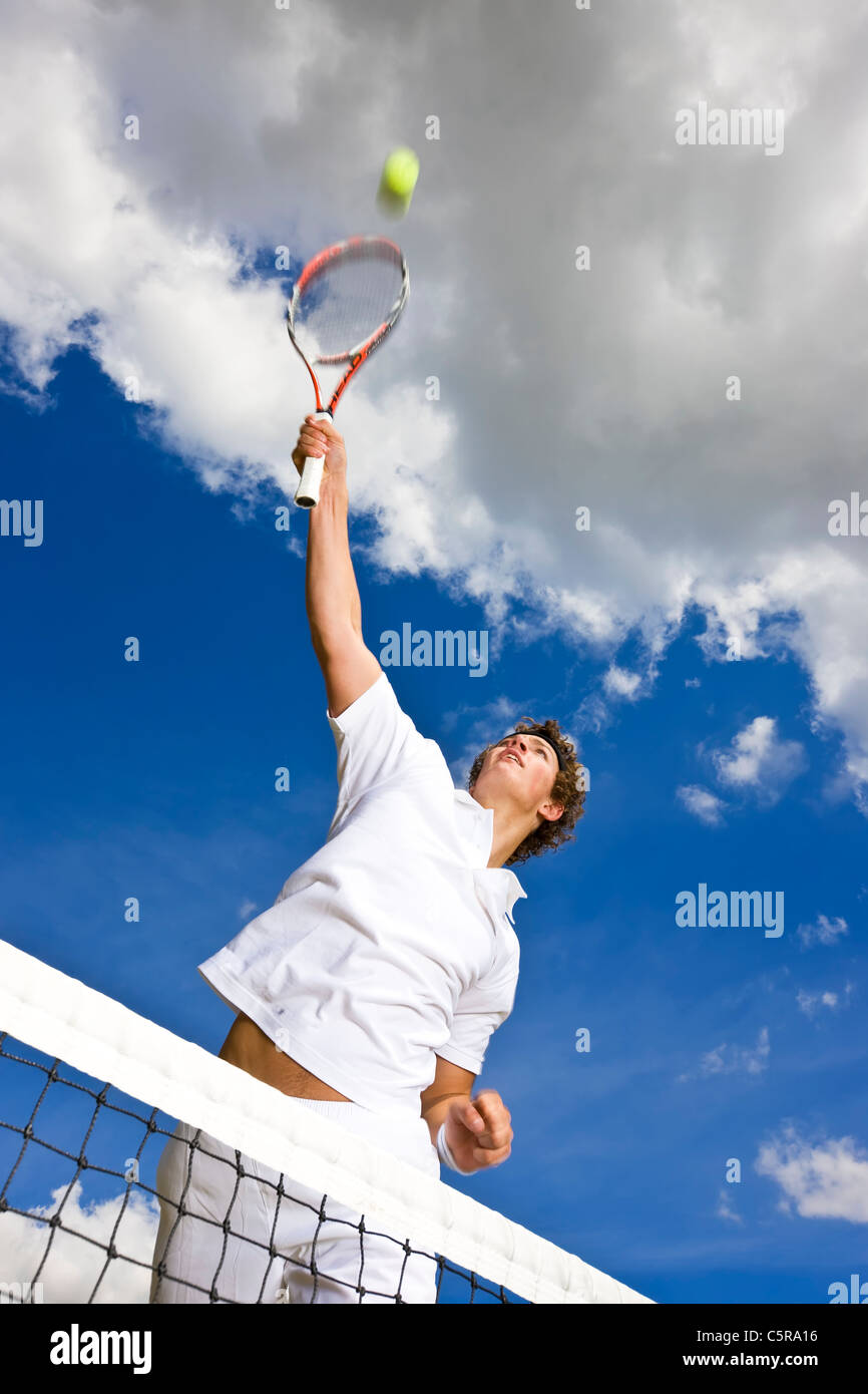 A tennis player stretches high above the net to smash ball for set point. - Stock Image