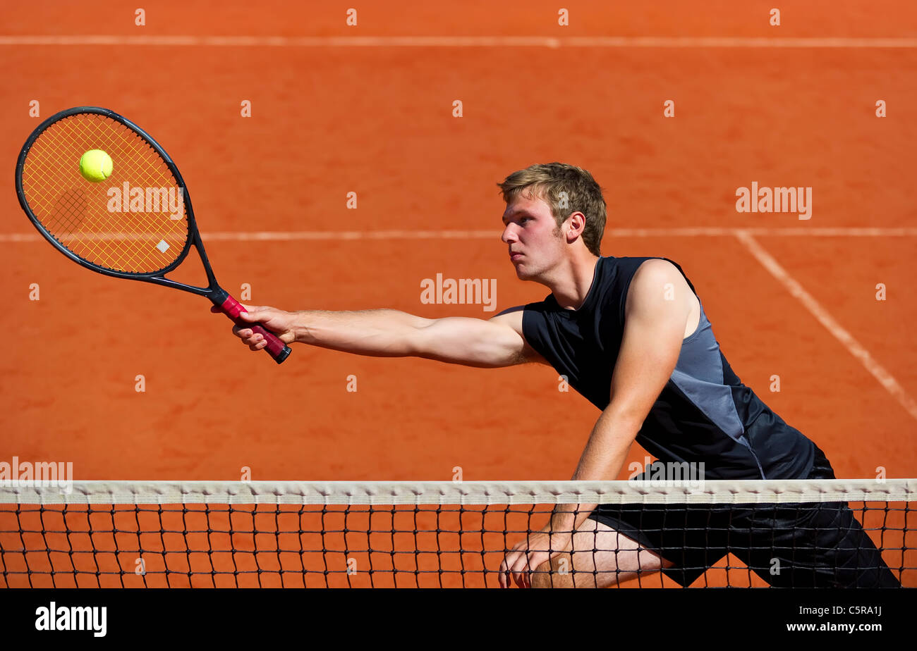 A tennis player at the net stretches to play ball. - Stock Image