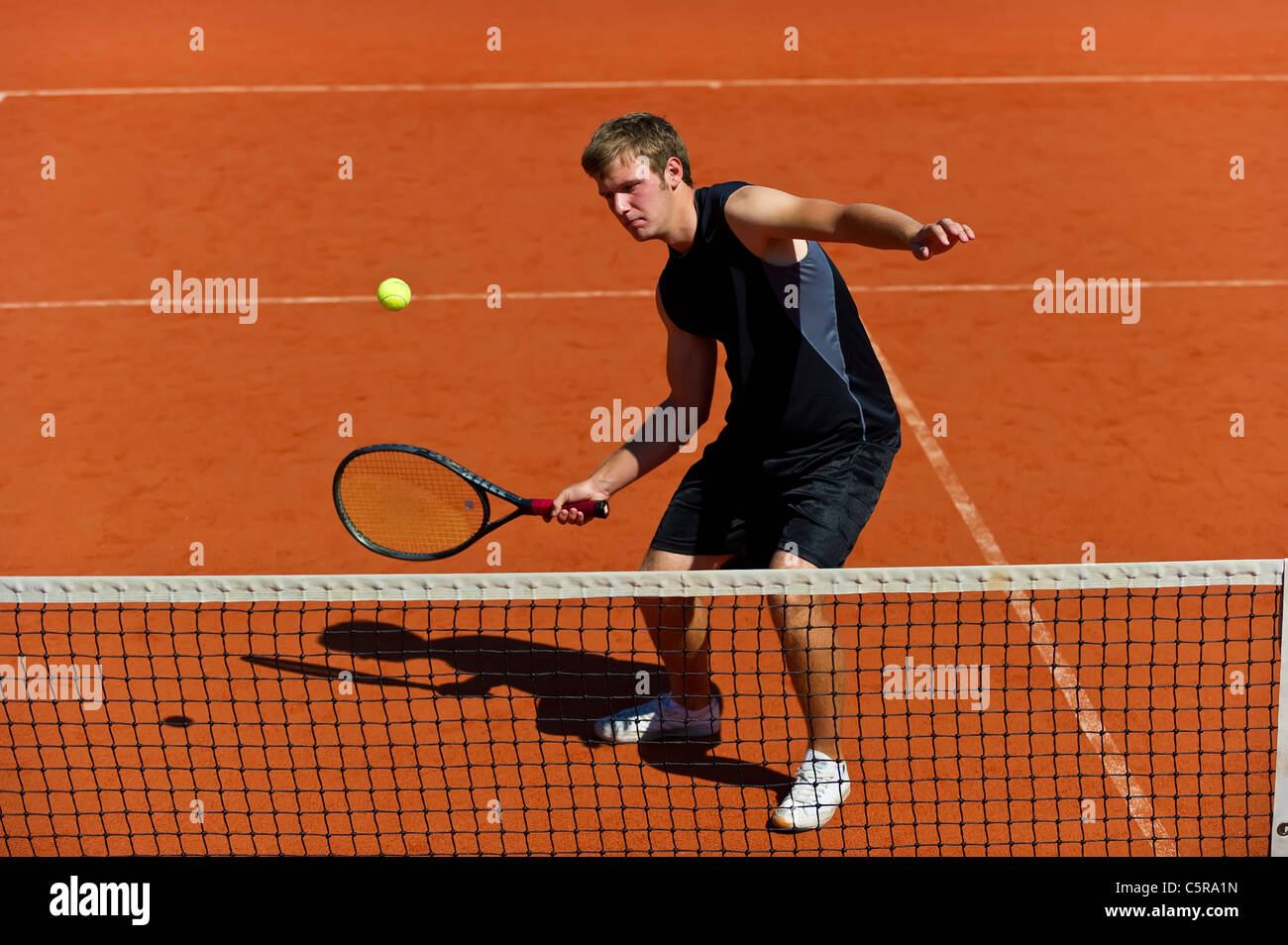 A tennis player up close to the net concentrates on volley - Stock Image