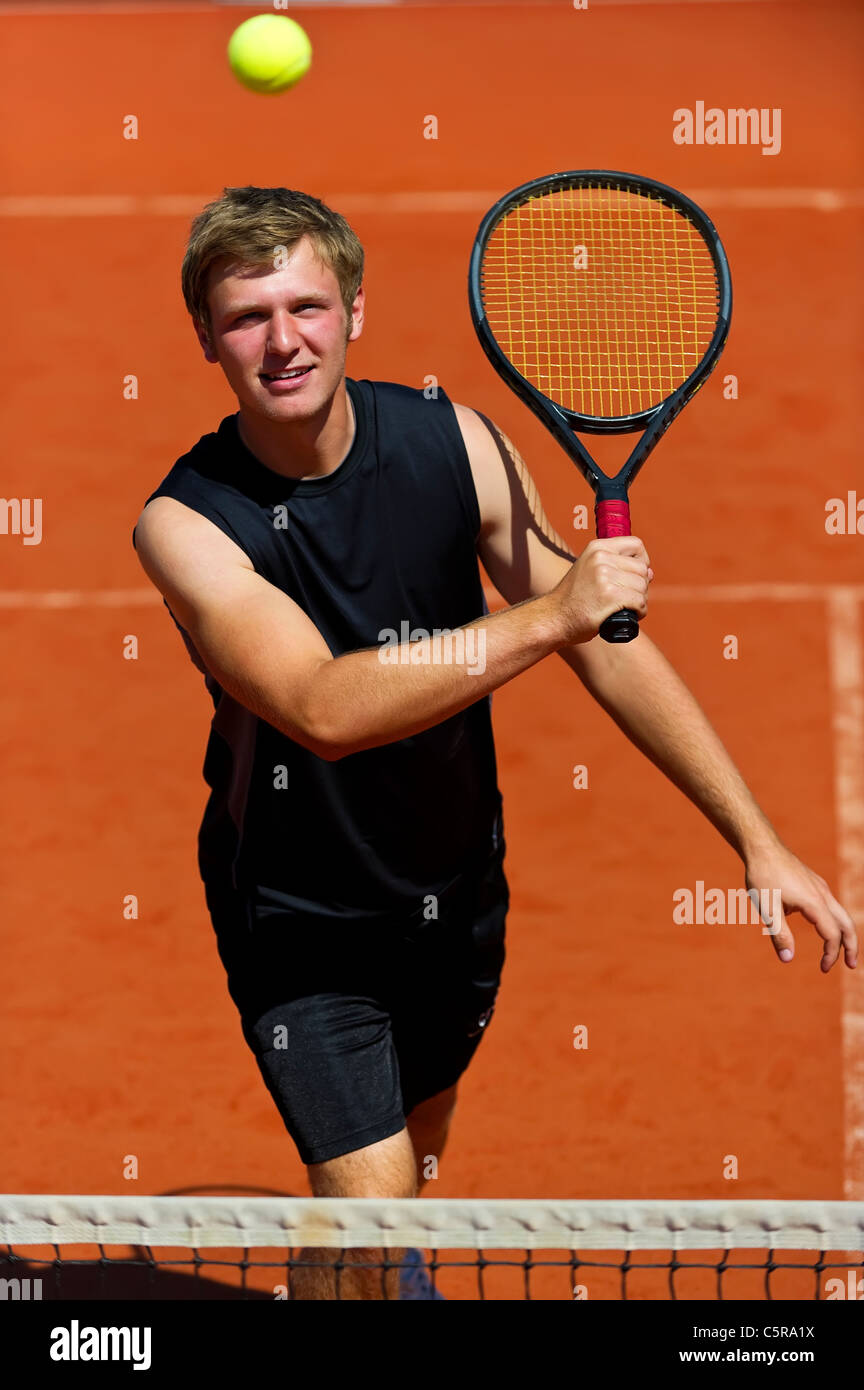 A tennis player smiles as he gets ready to volley ball. - Stock Image