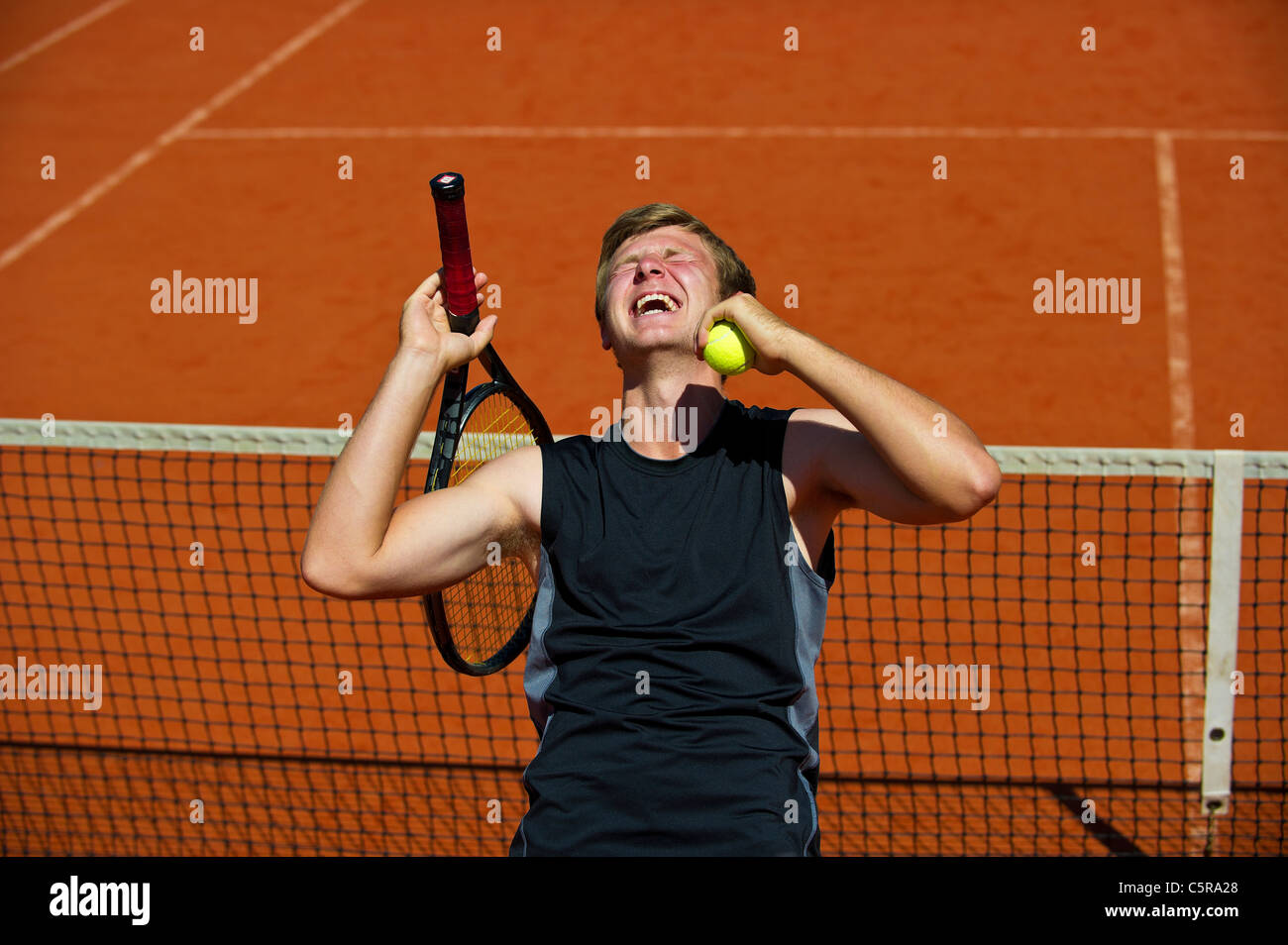 A tennis player celebrates winning the game set and match - Stock Image