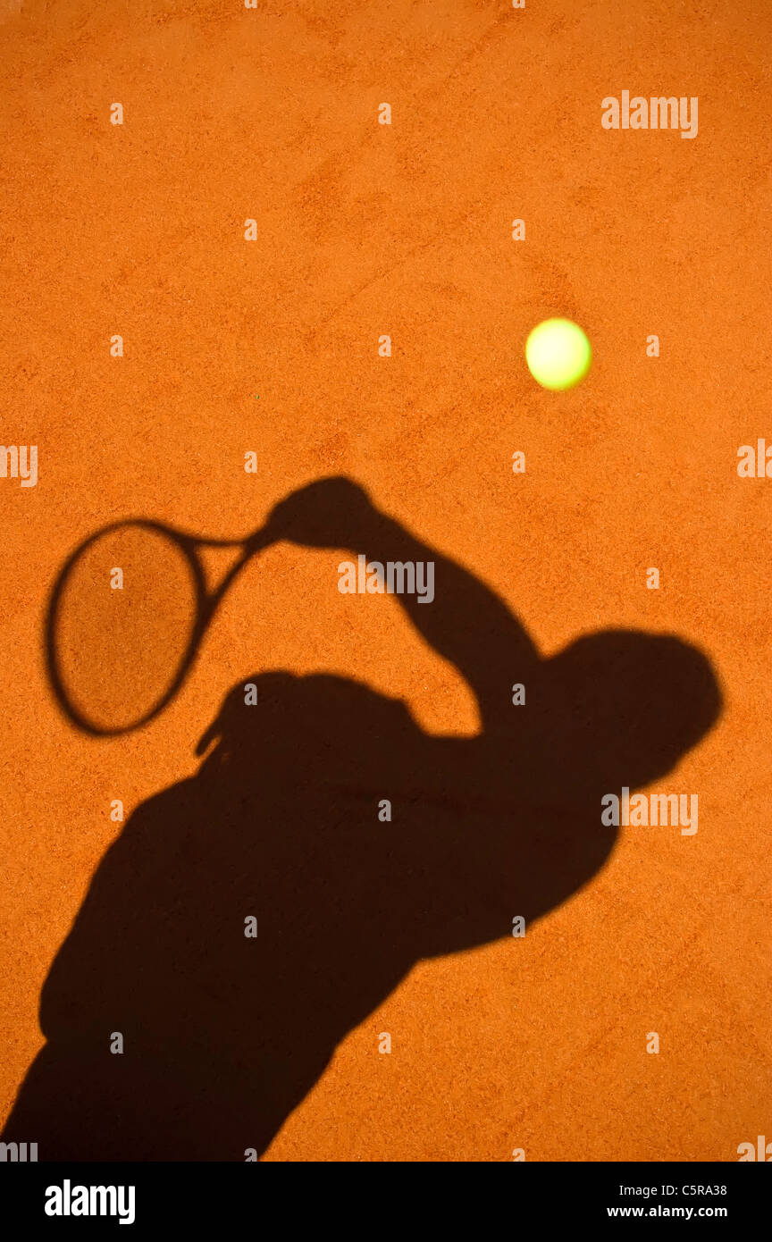 The silhouette of a tennis player serving. - Stock Image