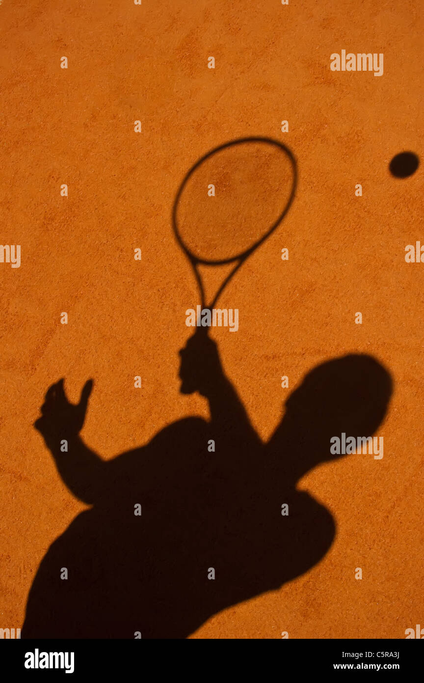 A tennis players silhouette playing the ball. - Stock Image