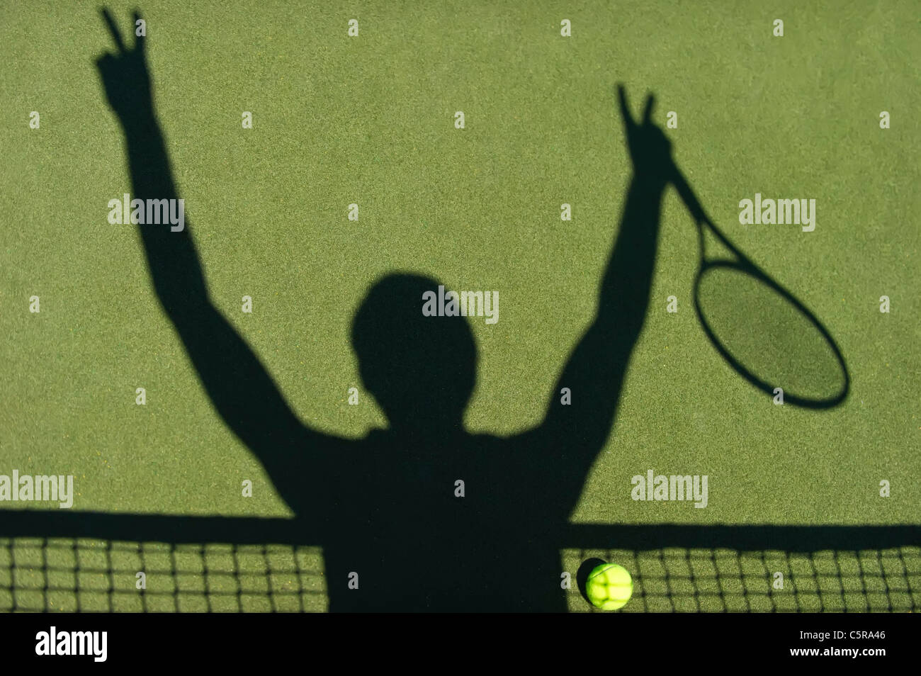 A tennis player celebrates being a winner. - Stock Image