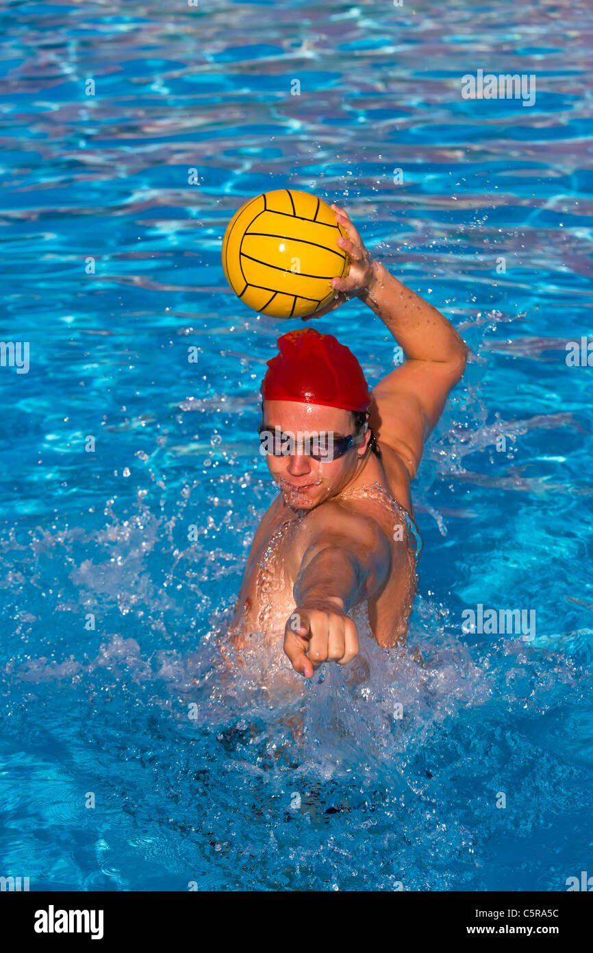 Water polo player lines up ball for goal. - Stock Image