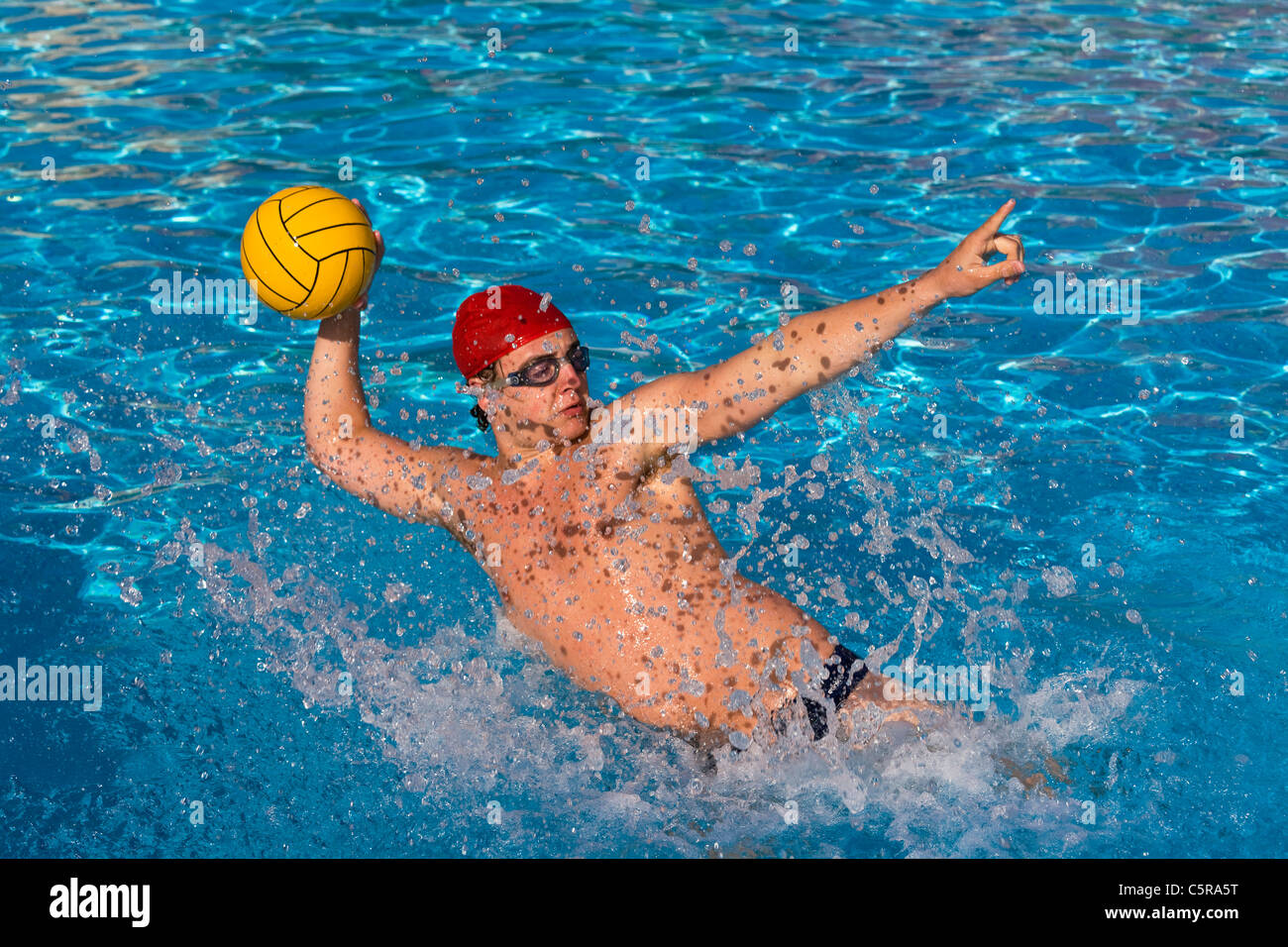 Water Polo player lines up direction of pass. - Stock Image