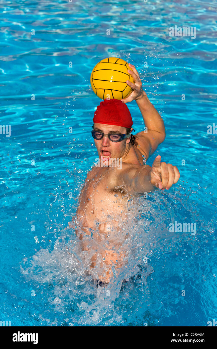 A Water Polo player shouts to team mate before passing ball. - Stock Image