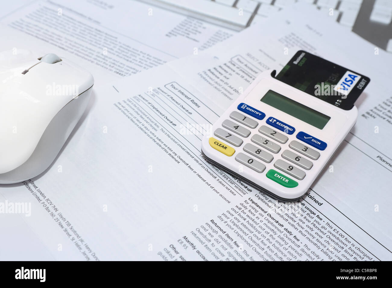 Internet Bank Card Reader with Card Inserted Sitting on Bank Statements with Other Credit Cards and Keyboard in - Stock Image