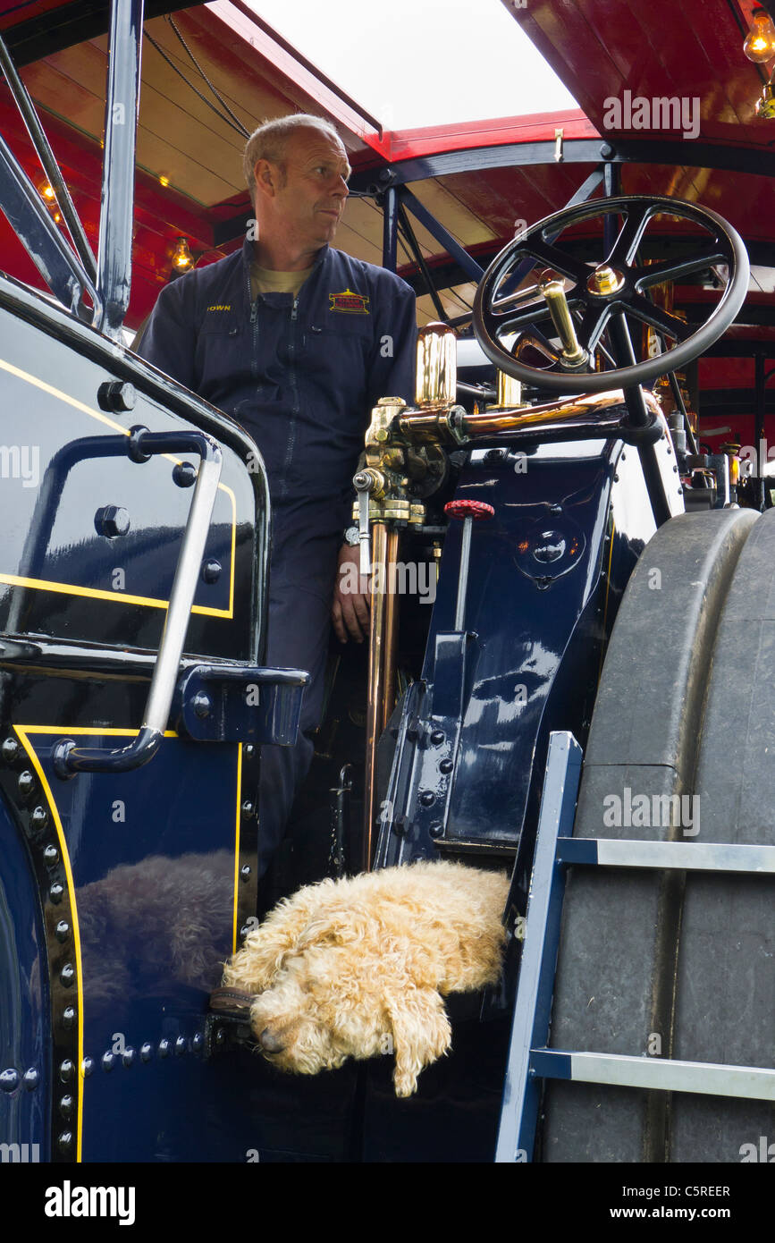 The driver of a traction engine with his pet dog asleep on the engine at Sandringham Flower Show 2011. - Stock Image