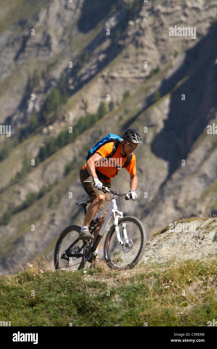 Italy, Livigno, View of man riding mountain bike near mountain - Stock Image