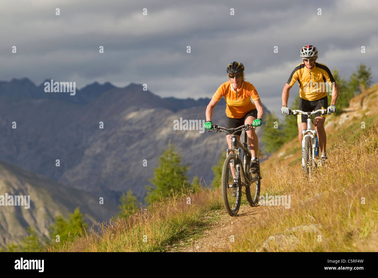Italy, Livigno, View of man and woman riding mountain bike - Stock Image