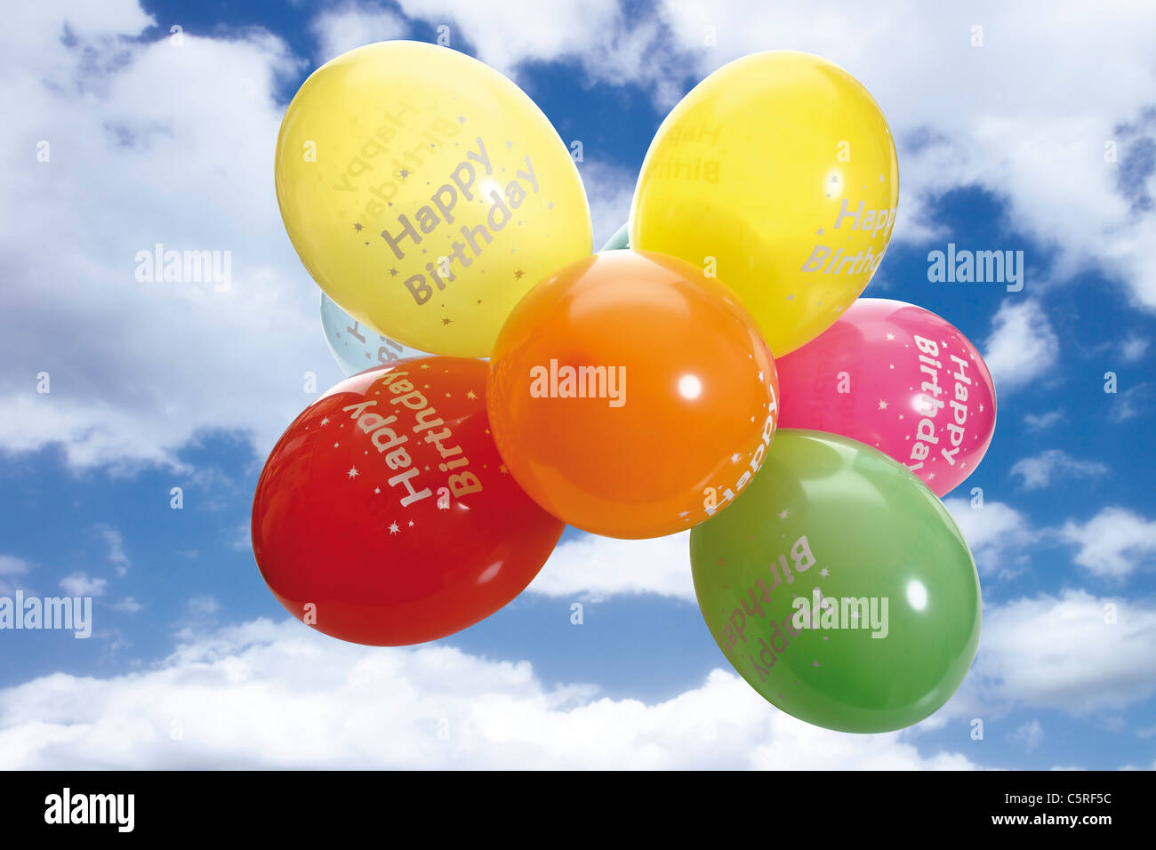 Colourful balloons against cloudy sky - Stock Image