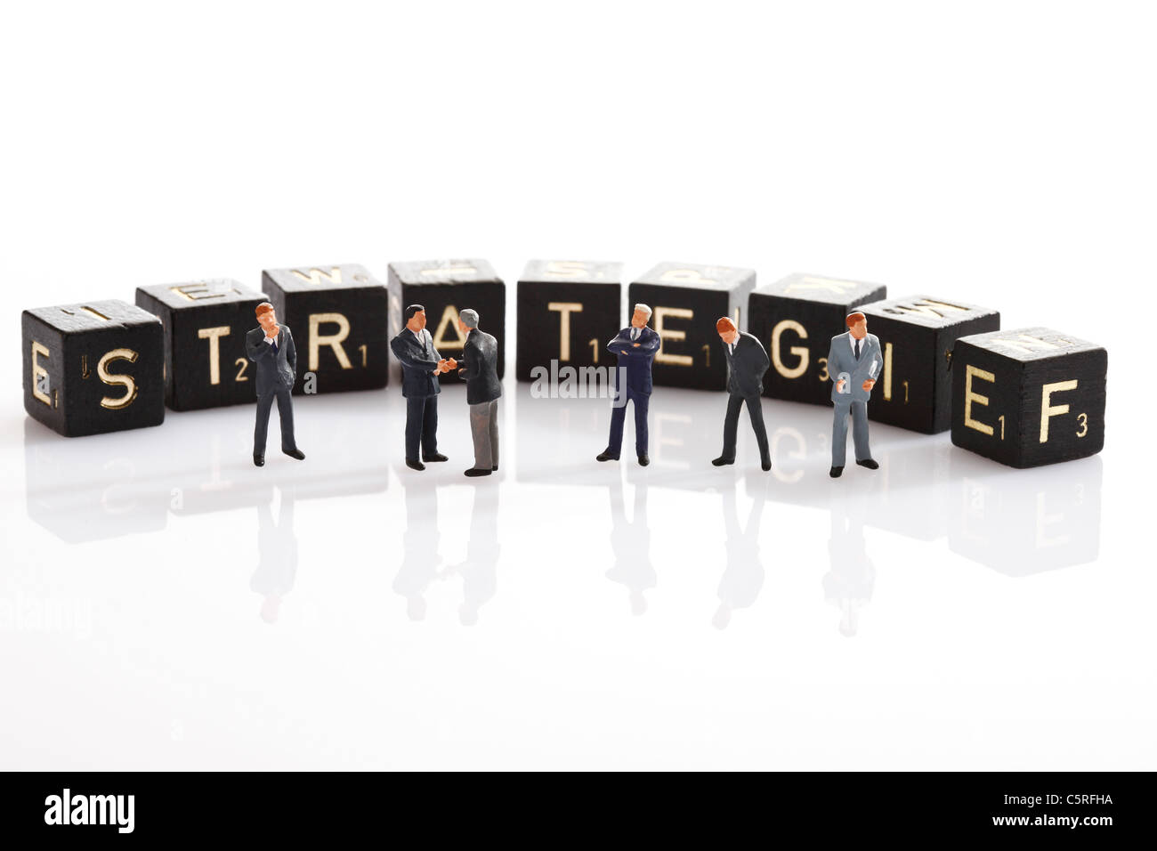 Scrabble tiles forming the single word strategy, in foreground Business men figurines - Stock Image