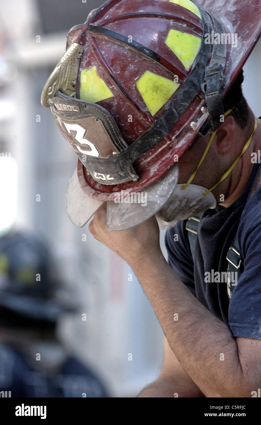 Fireman wipes away a tear at ground zero, World Trade Center following 911 terrorist attacks - Stock Image