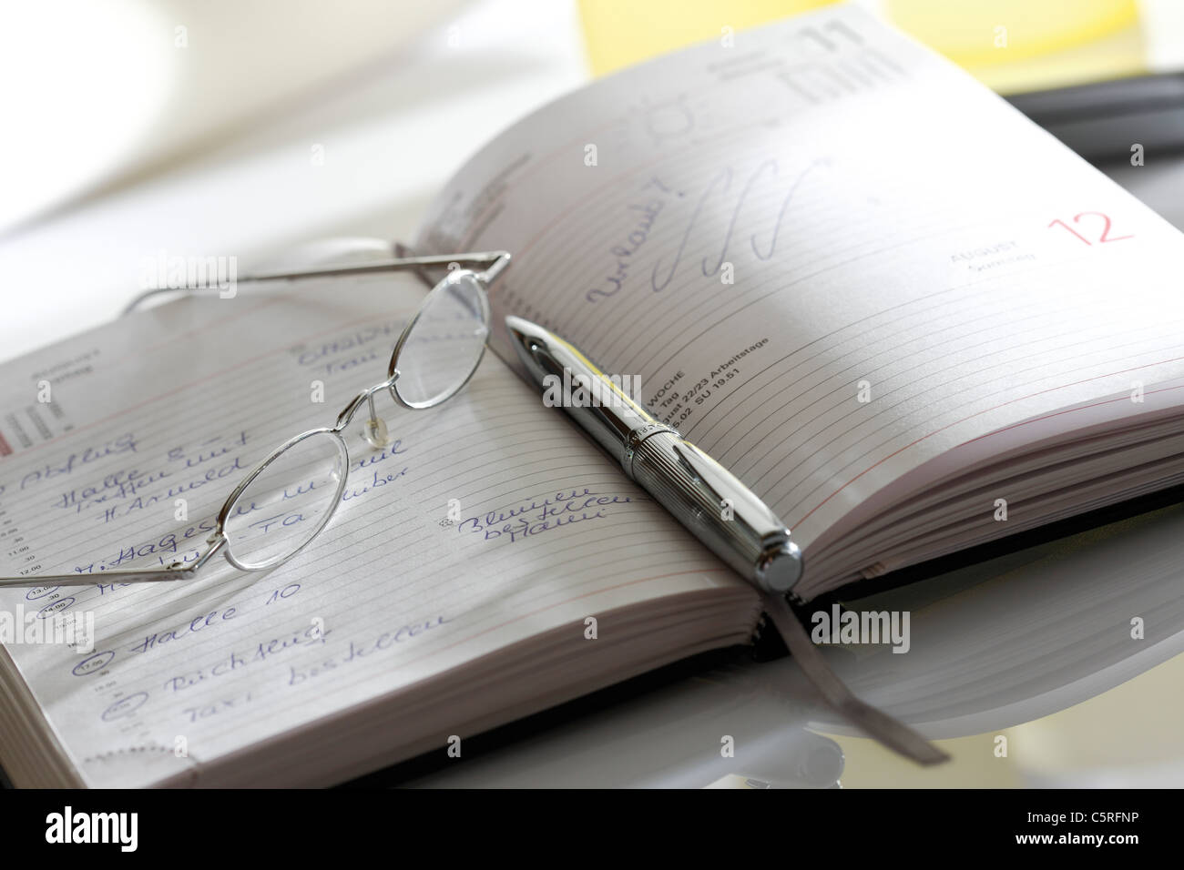 Notebook, eyeglasses and pen, close-up - Stock Image