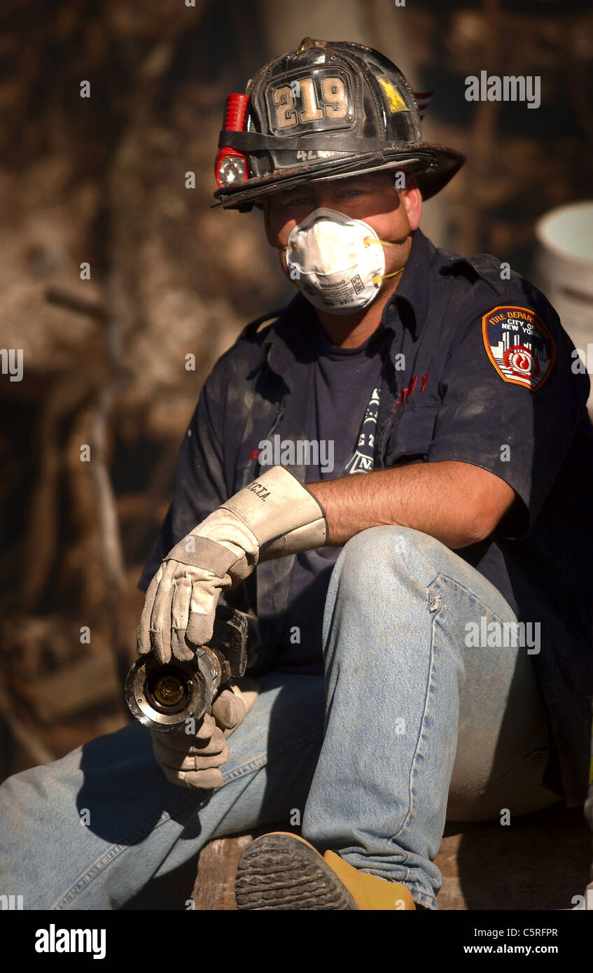 fireman rests at ground zero, the World Trade Center following the 911 terrorist attacks - Stock Image