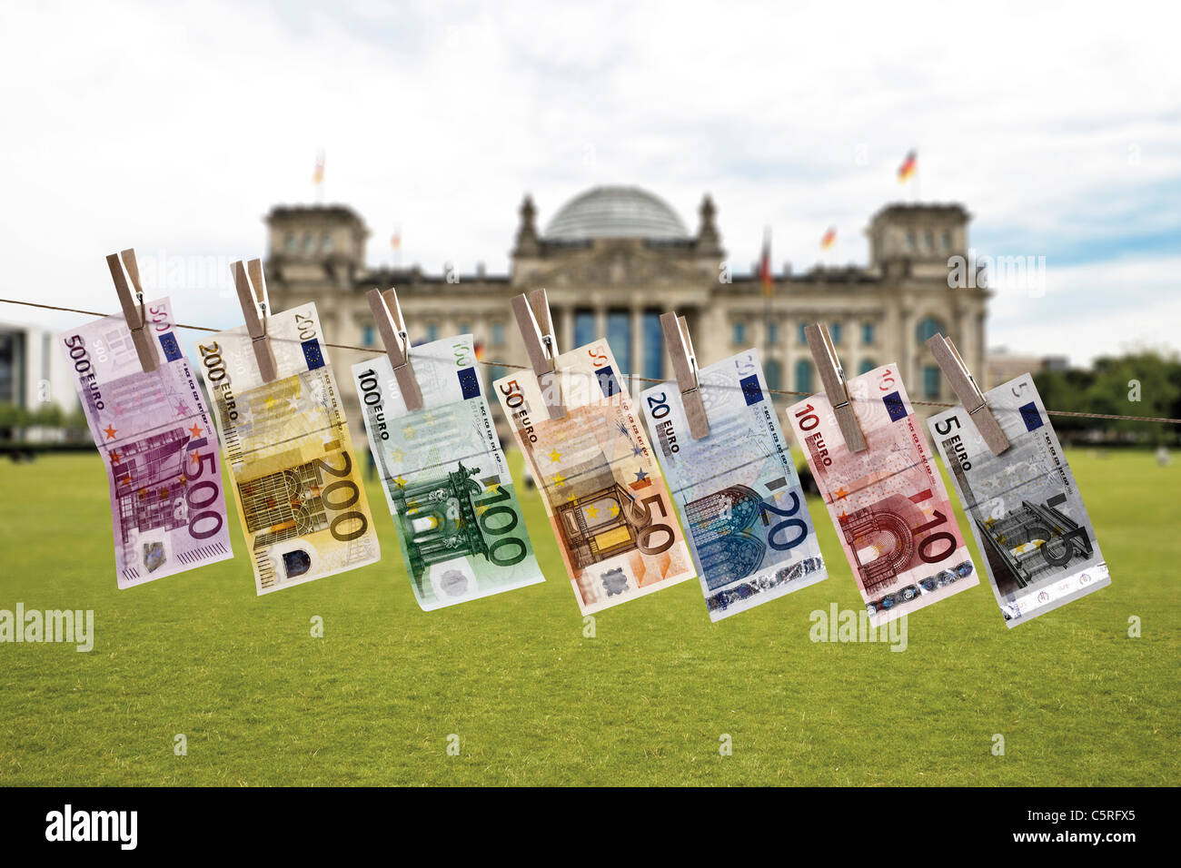 Germany, Berlin, Euro bank notes hanging on clothesline, Reichstag building in background Stock Photo