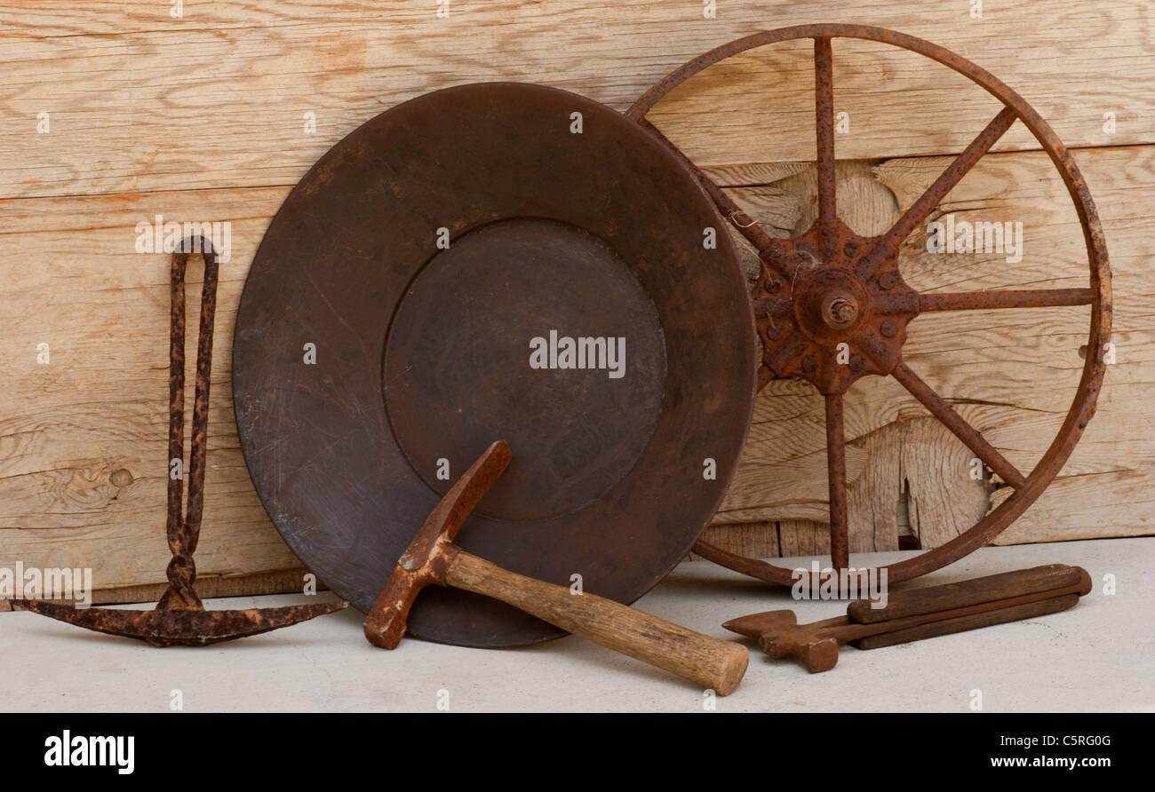 Old mining tools: wheel, picks, ax, gold pan. - Stock Image