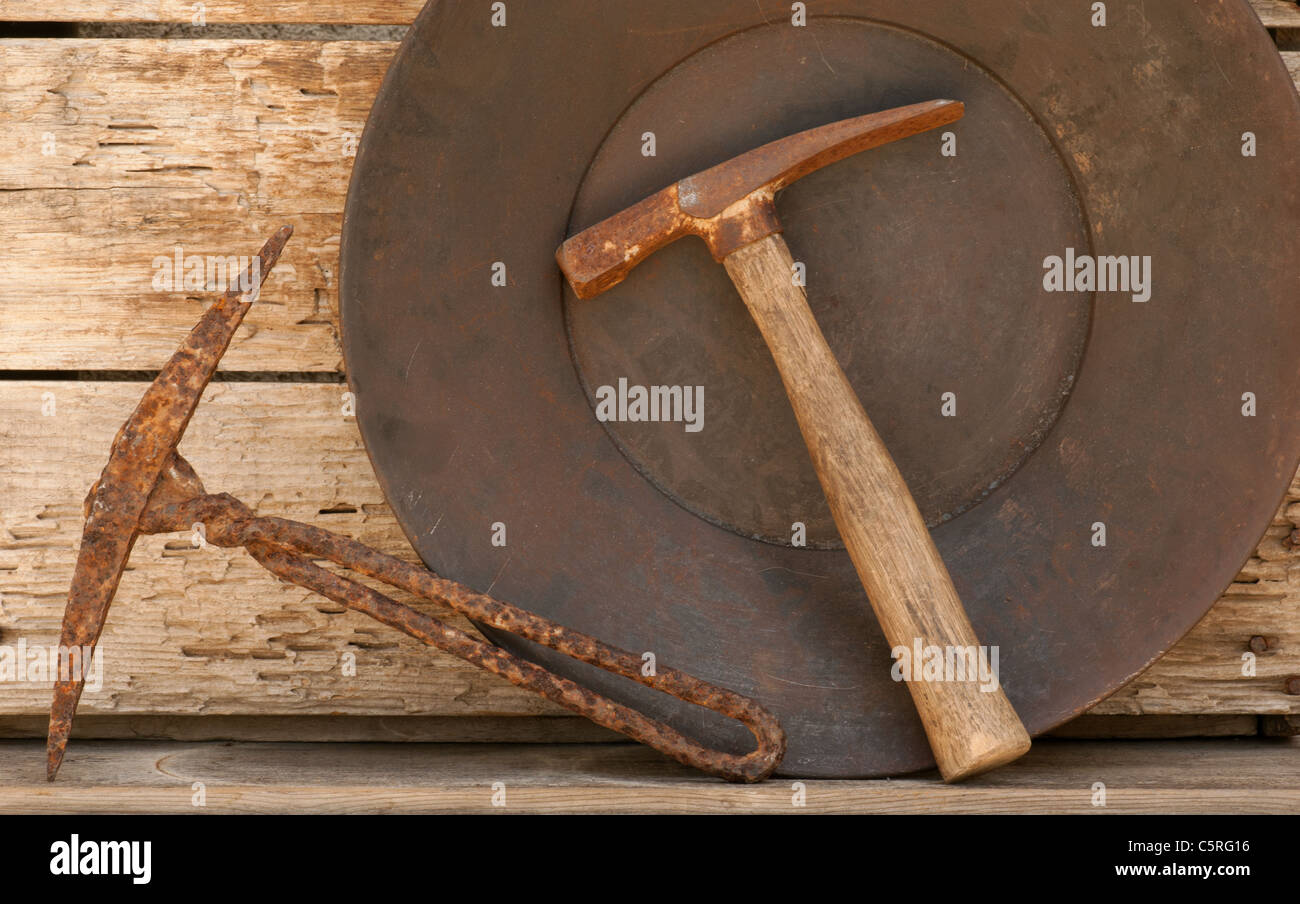 Rusted mining gold panning picks with old pan. Weathered wood shelf background. Stock Photo