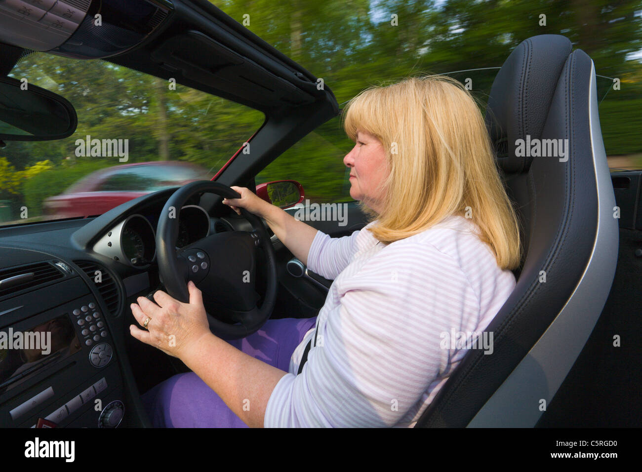 Woman driving a convertible, open top, Mercedes sports car - Stock Image