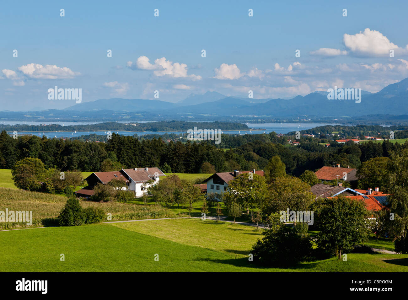 Germany, Bavaria, Chiemgau Alps, Herrenchiemsee, Chiemsee, View of village with island and freshwater lake in background - Stock Image