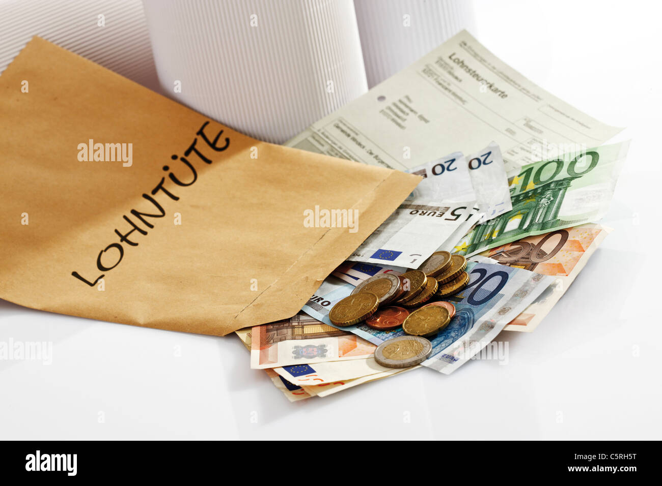 Tax card, Euro coins and Euro bank notes in wage packet - Stock Image