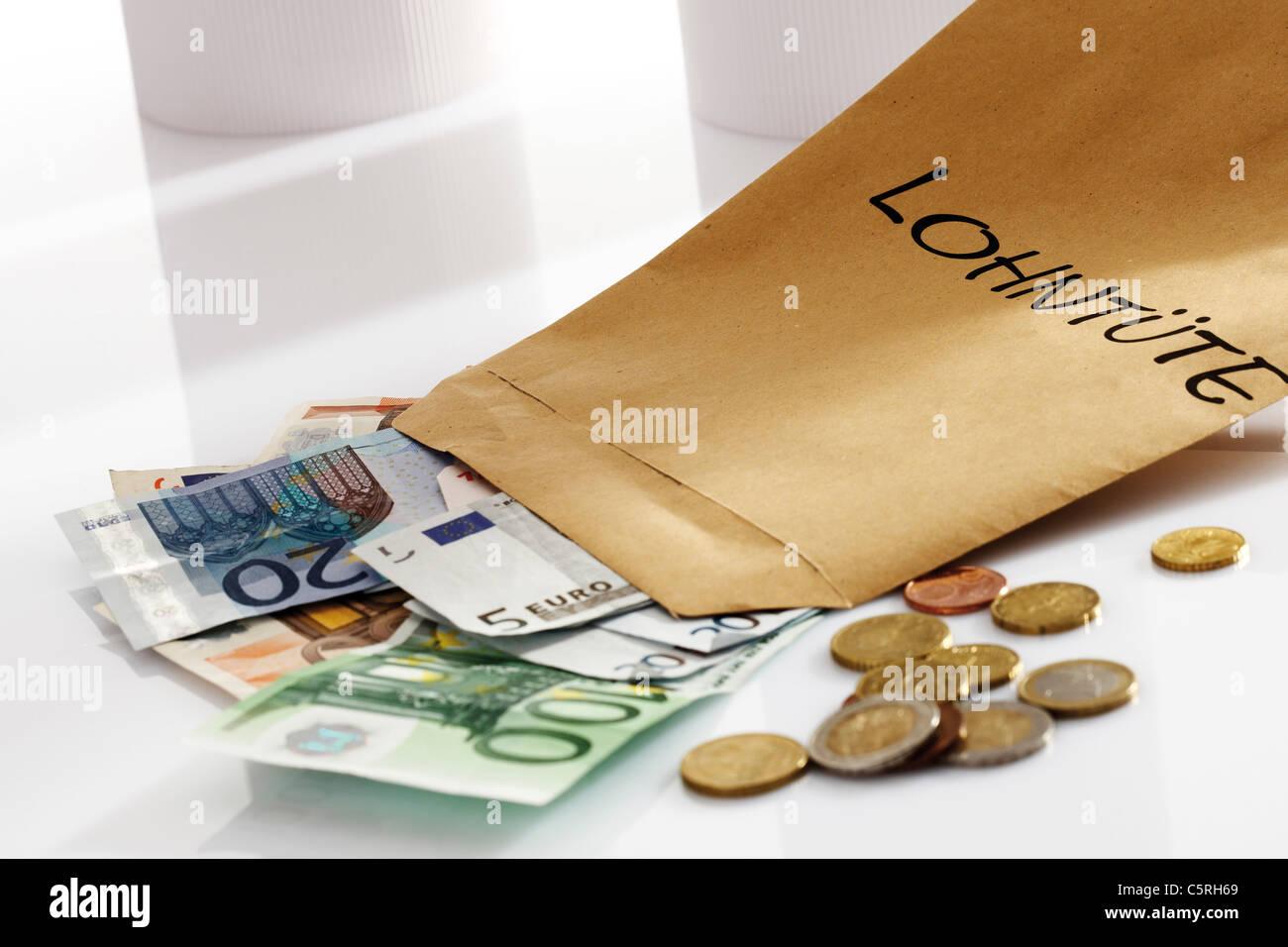 Wage packet, Euro coins and Euro bank notes, close-up - Stock Image
