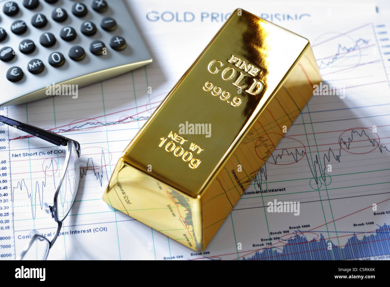 Gold bullion barr on a stocks and shares chart - Stock Image