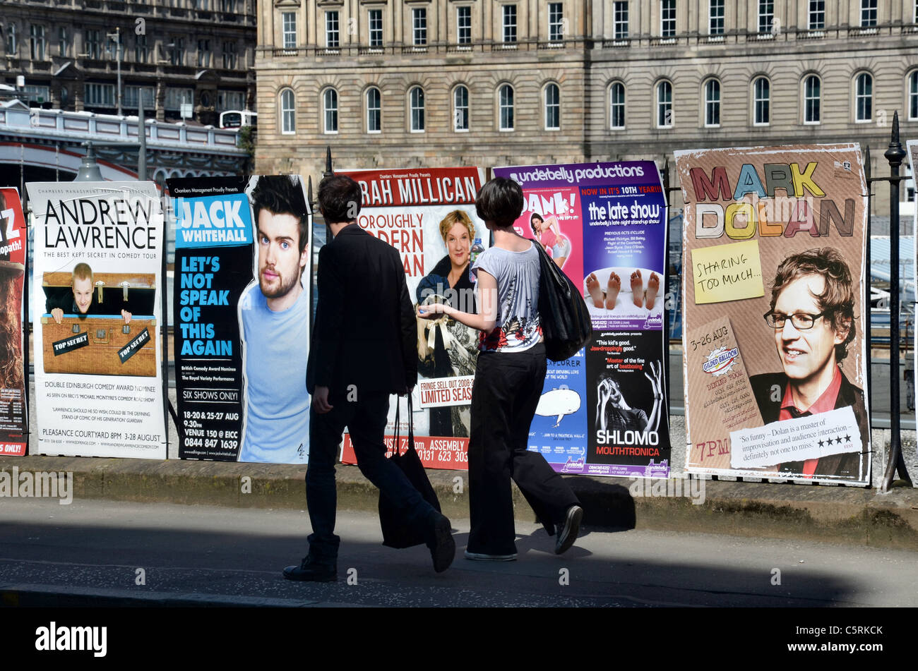 A couple walk by posters advertising shows on the 2011 Edinburgh Festival Fringe with the New Town as a backdrop. - Stock Image