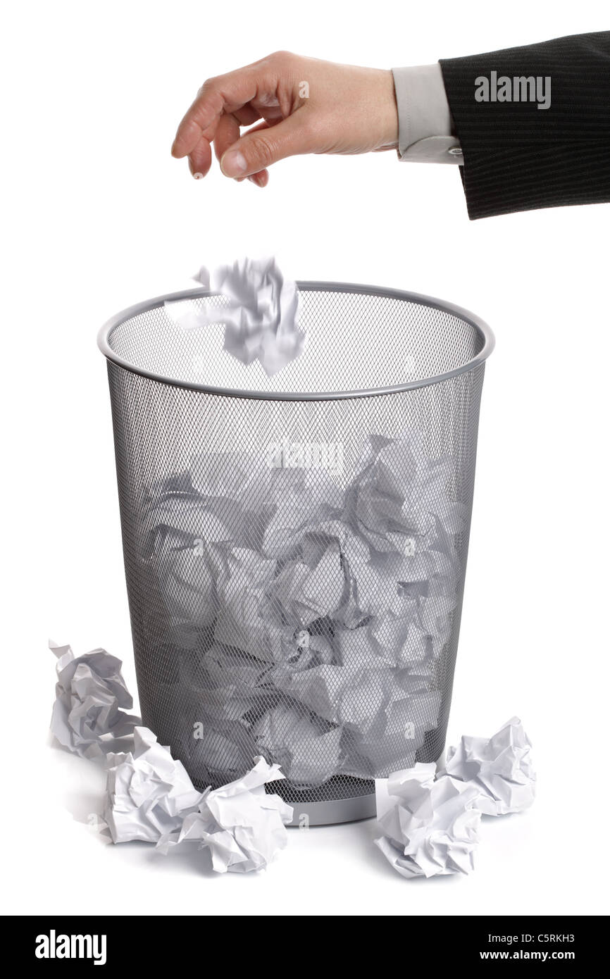 Hand dropping paper into wastepaper bin - Stock Image
