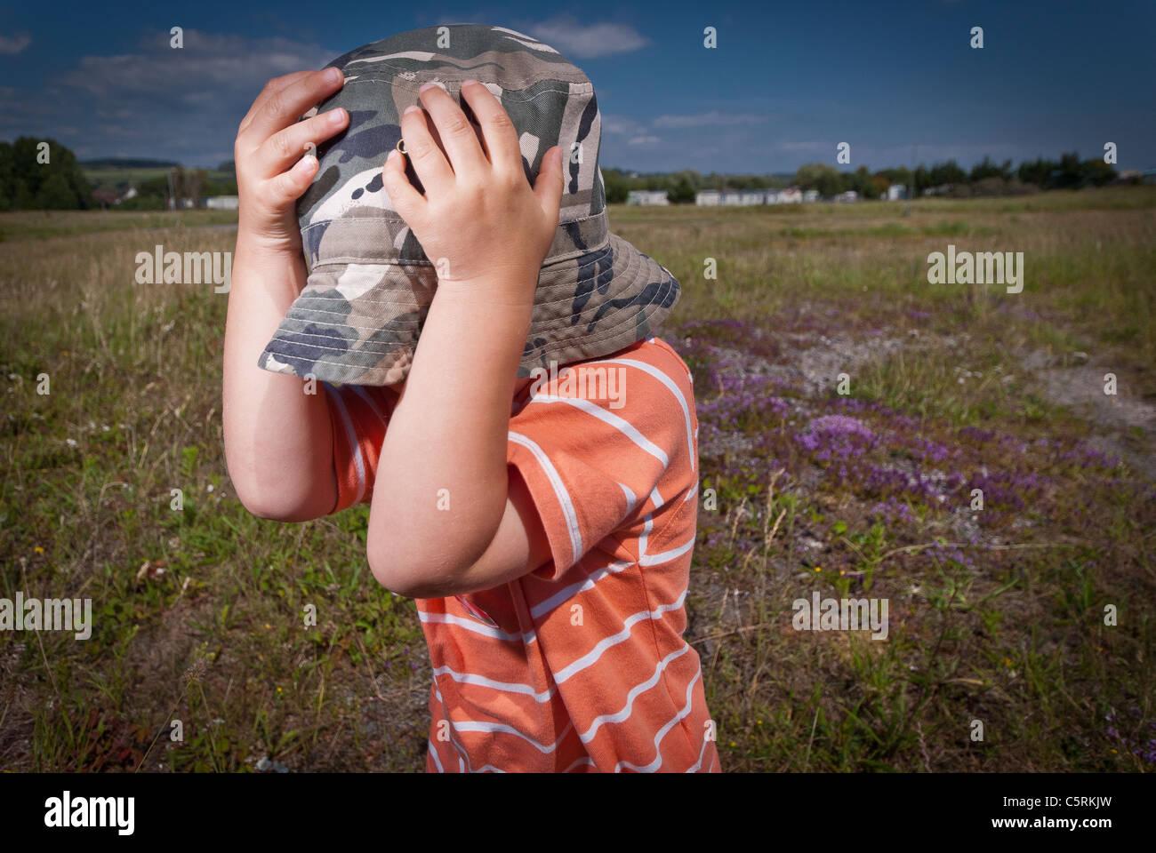 boy hiding beneath hat in field - Stock Image