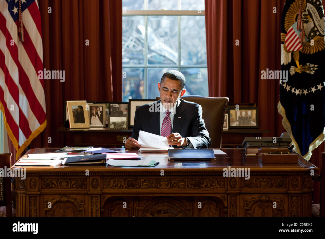 President Barack Obama reviews his prepared remarks on Egypt at the Resolute Desk in the Oval Office, Feb. 11, 2011. - Stock Image