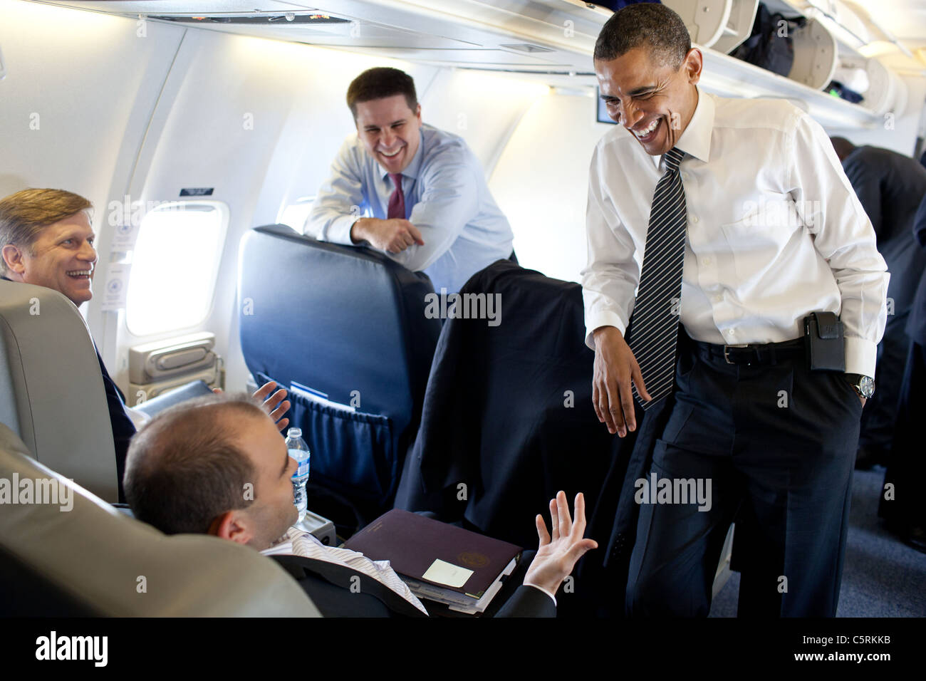 Obama jokes and laughs with Advisors on Air Force One - Stock Image