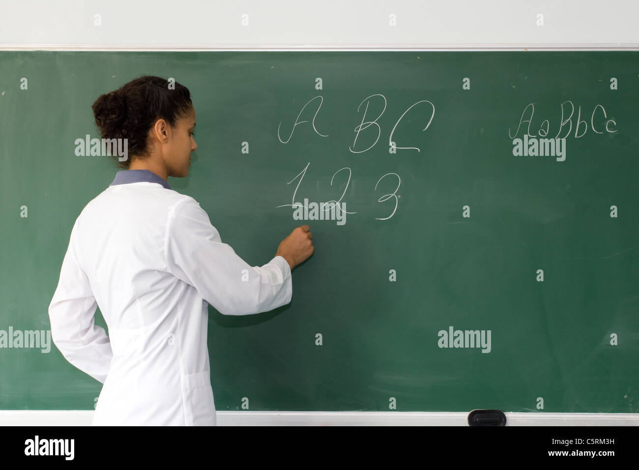 adult teacher is standing near chalkboard and writing - Stock Image