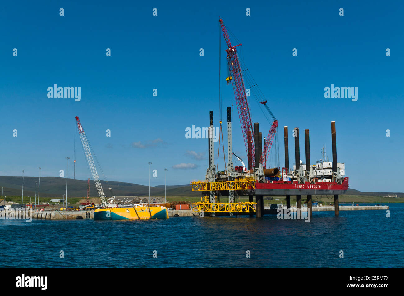 dh Lyness Pier HOY ORKNEY Fugro Seacore positioning platform rig and yellow Wellos Penguin renewables - Stock Image
