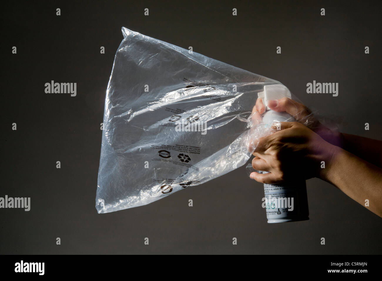 A plastic bag is filled by an aerosol inhalant gas can for illegal use as a drug. - Stock Image