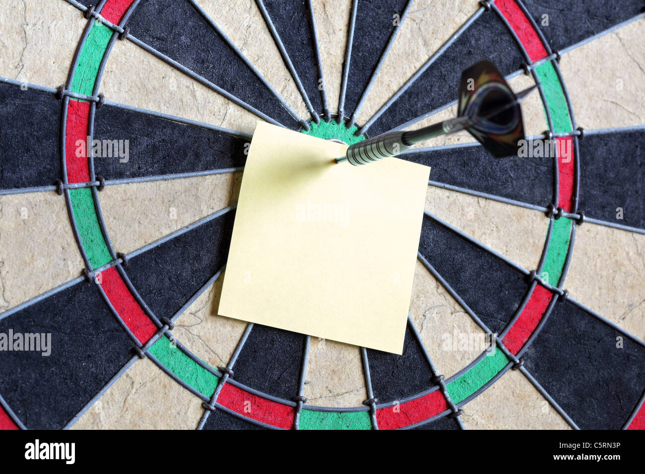Yellow sticky note on dartboard - Stock Image