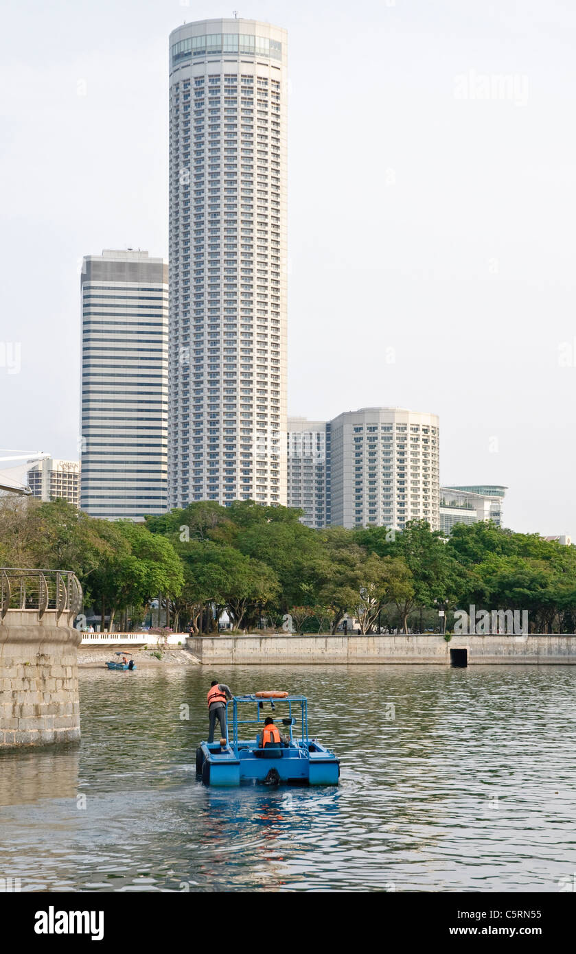 Men collecting garbage and filth from Singapore River, office buildings, Singapore, Southeast Asia, Asia - Stock Image