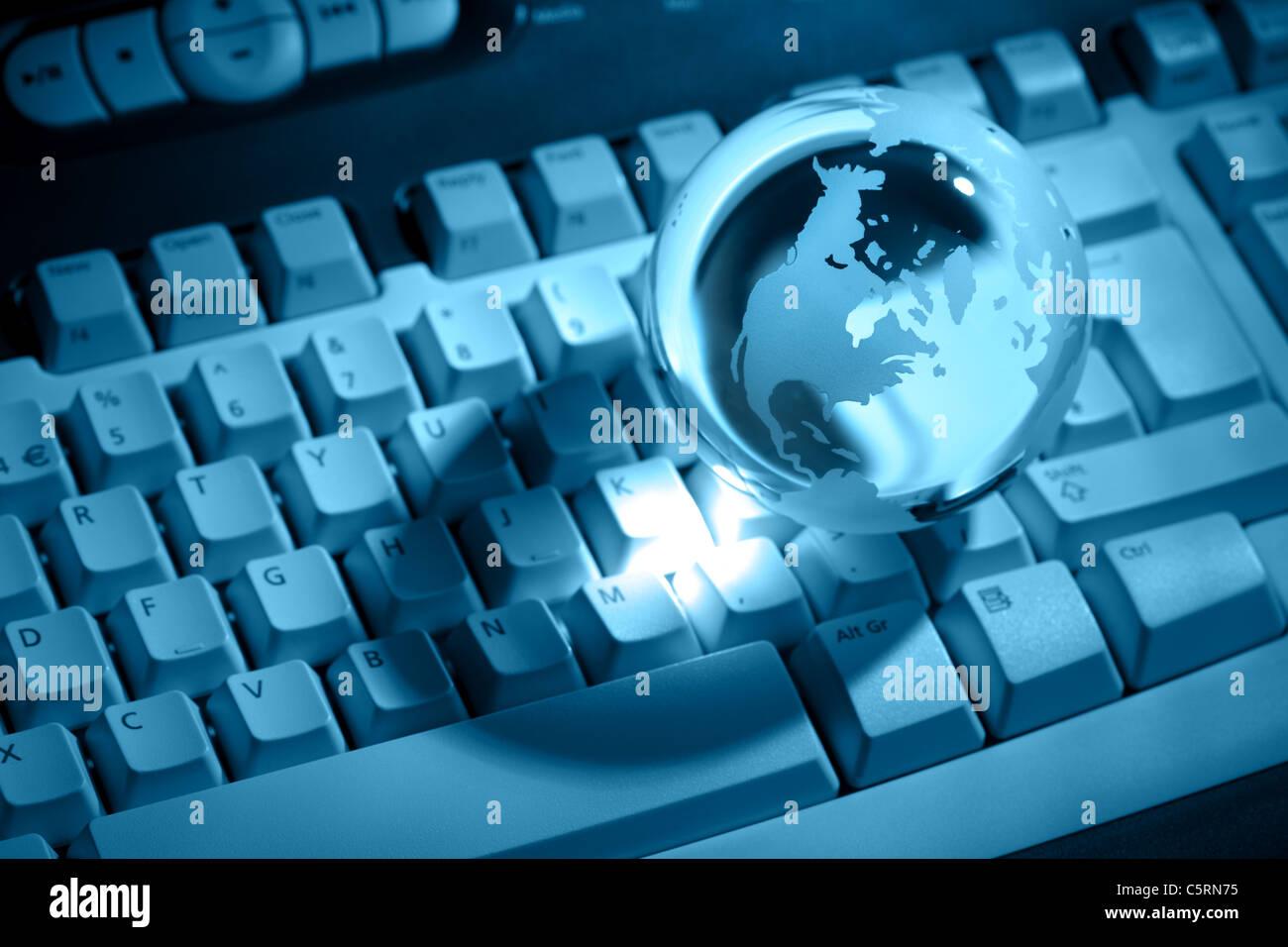 Crystal globe on keyboard - Stock Image
