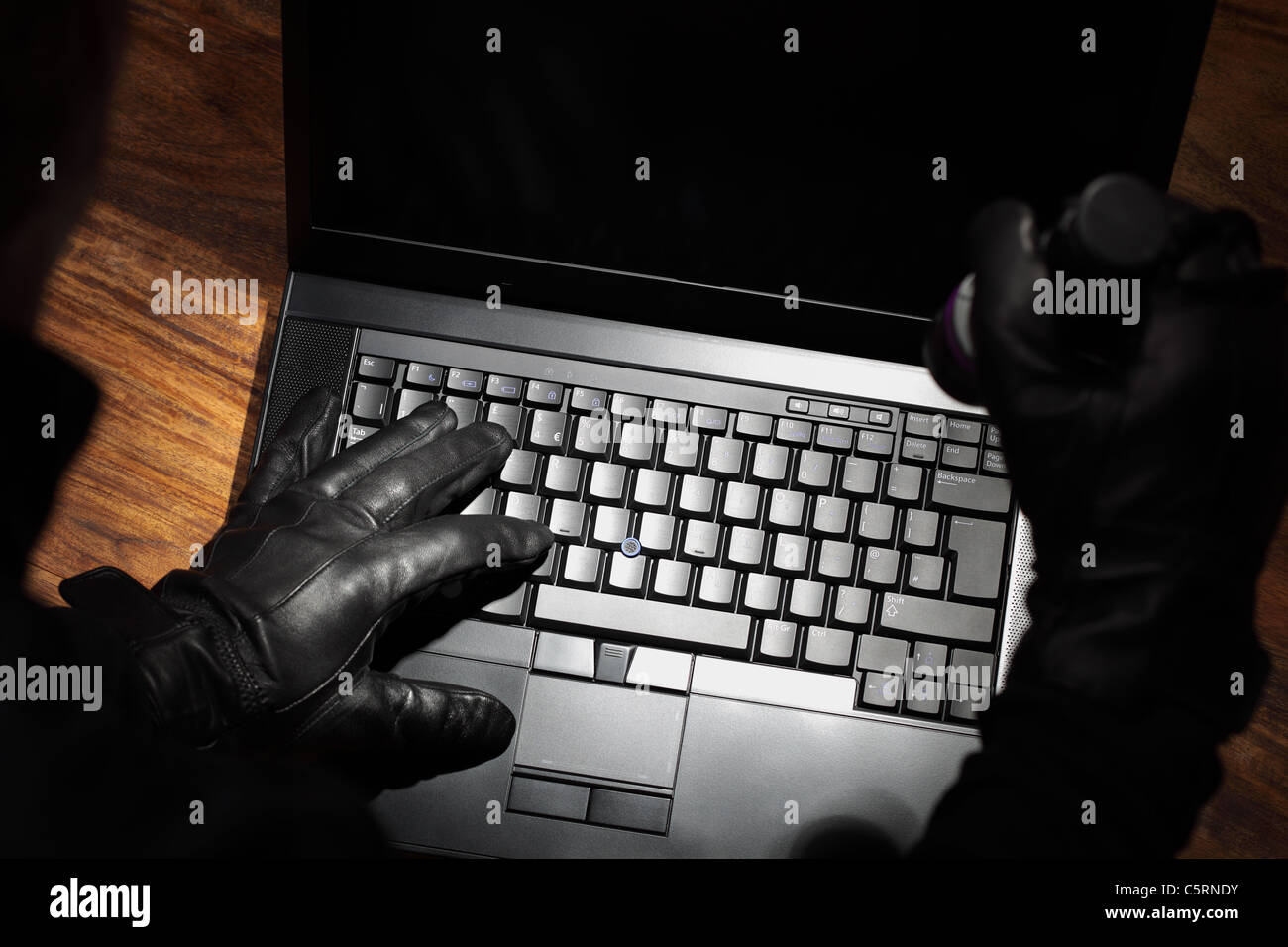 Man stealing data from a laptop - Stock Image