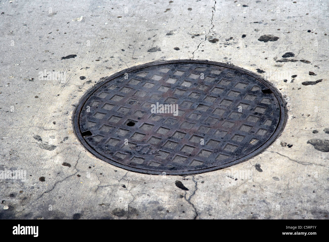 steam rising from metal manhole cover in the street Nashville Tennessee USA - Stock Image