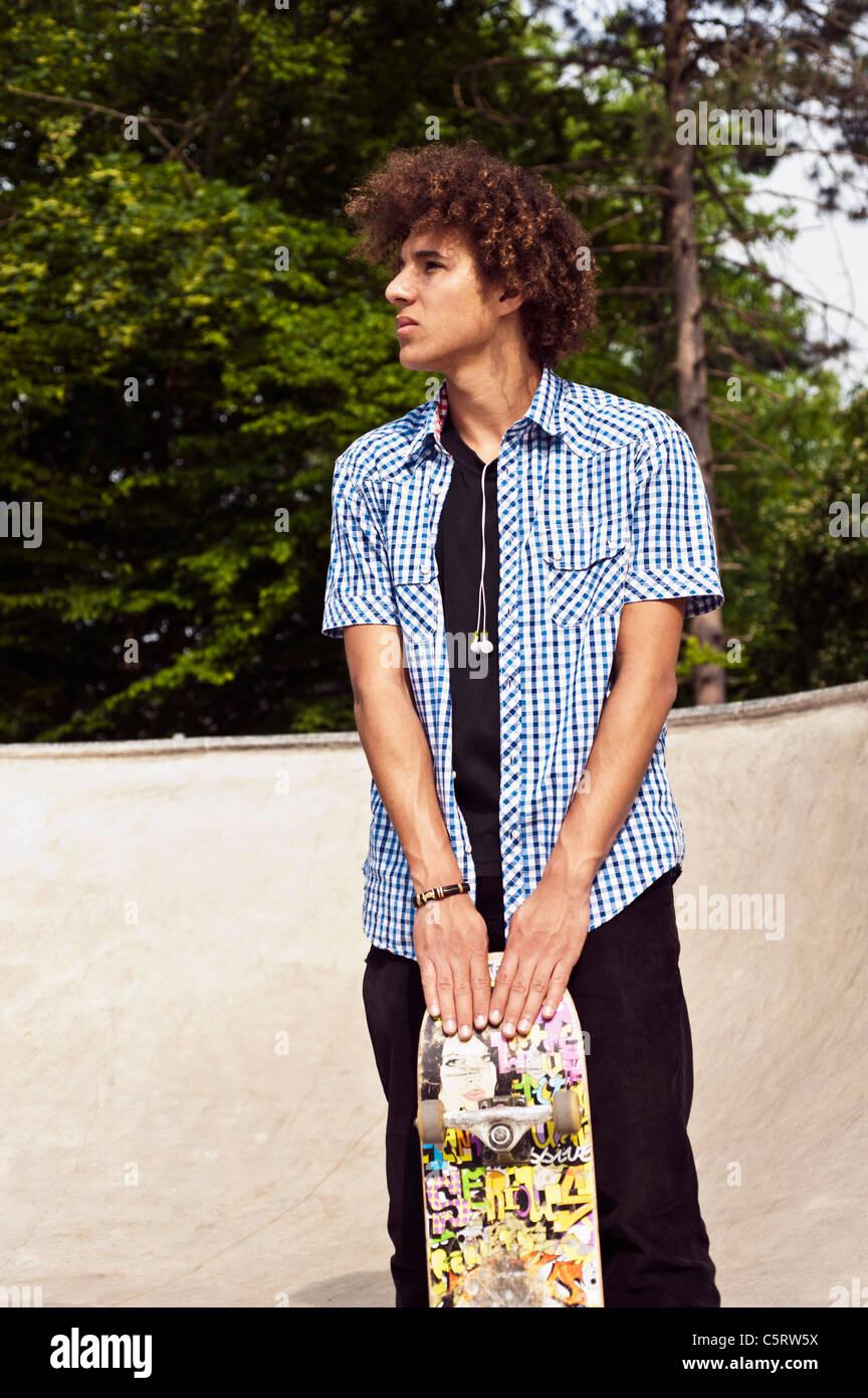 Germany, NRW, Duesseldorf, Man holding skateboard at public skatepark - Stock Image