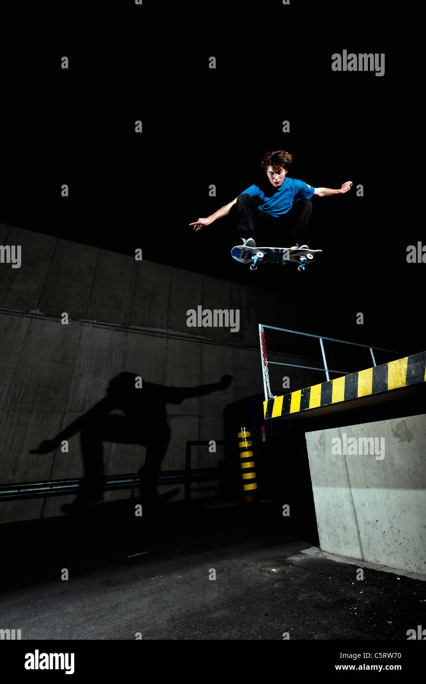 Germany, North Rhine-Westphalia, Duesseldorf, View of young skateboarder performing stunt at night - Stock Image