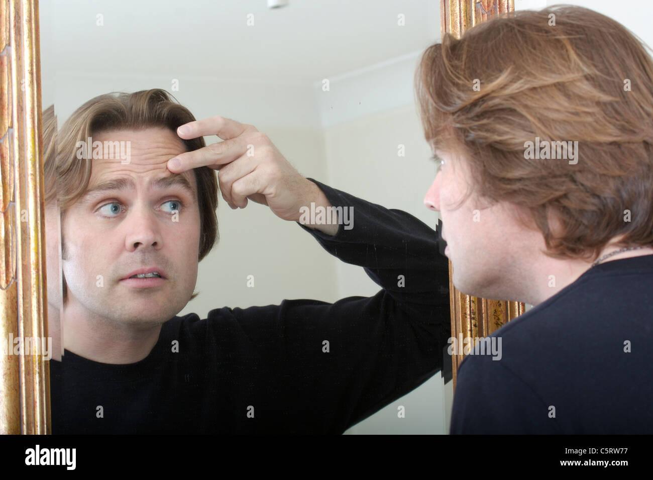 man looking into mirror - Stock Image